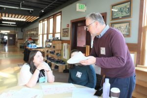 Two female students sit at round table while Dale Kruse, opera creation instructor, stands and gives them directions.