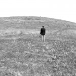 Person standing in empty field.