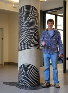 Student poses with artwork on a pillar.