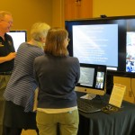 Faculty members studying a TV screen.