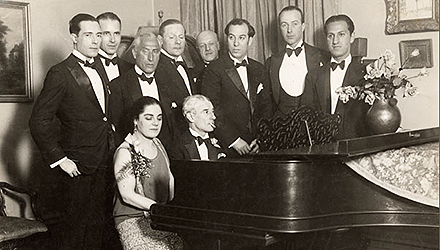 Maurice Ravel at piano with group of people