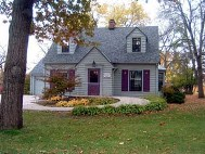 A gray house with a tree in the front yard