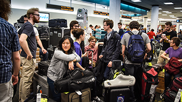 St. Olaf students with instruments at airport while traveling to Cuba