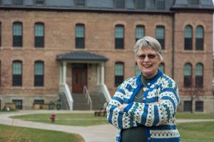 Beth Olson Spande '66 stands in front of Old Main