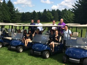Professors from the St. Olaf Psychology Department pose for a photo while sitting in golf carts.