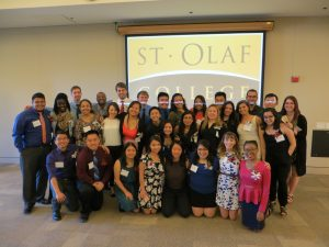 a group of students posses in front of St. Olaf logo
