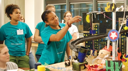 Participants in St. Olaf College's Physics and Engineering Camp work on building a Rube Goldberg machine.