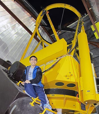Eric Topel '15 sits on the 2.3-meter telescope at the Wyoming Infrared Observatory on Mt. Jelm. Topel is spending time at the facility as part of an NSF research program.