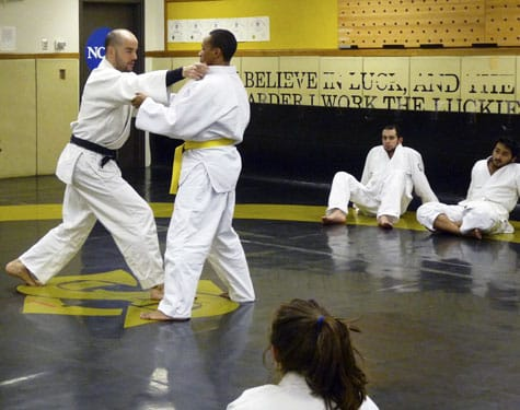 "Assistant Professor of Philosophy Danny Muñoz-Hutchinson (left) demonstrates a technique during his ""Zen and the Art of Judo"" course."