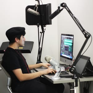 A student named Salvador Alvarez using the DiSCO room dedicated to audio recording.
