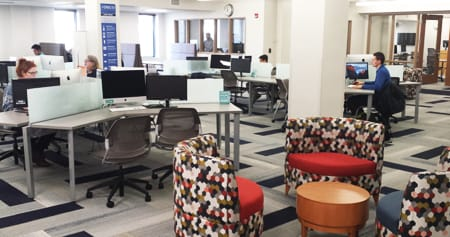A photo of the new DiSCO space in the library that shows workstations and colorfully patterned furniture.