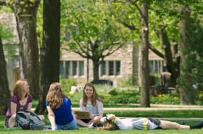 four students -- including one seated and one prone -- lounge outside on the grass on a beautiful spring day